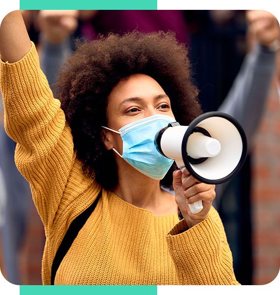 Young woman wearing a mask protesting with a megaphone